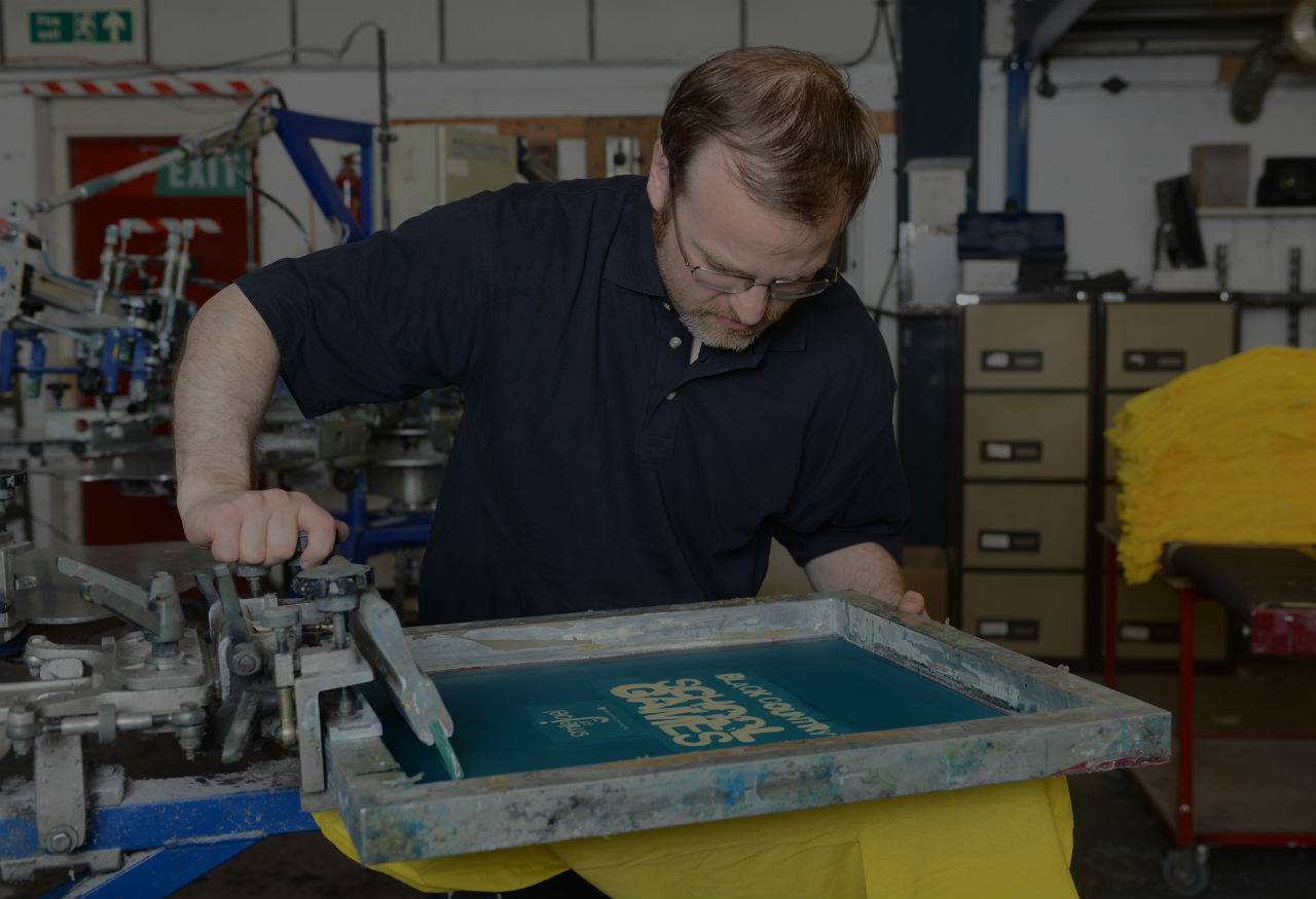 A man screen printing a t-shirt